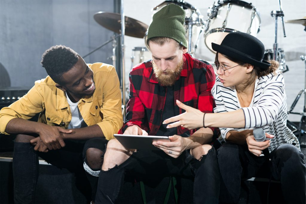Three young musicians while discussing in rehearsal studio